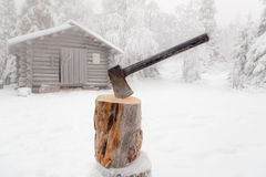 Ax stuck in log of wood. Ax stuck in log of wood on the background of the winter forest and huts Royalty Free Stock Photo