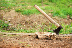 Ax stuck in a stump against a background of green grass Royalty Free Stock Photo