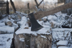 The ax stuck in the stump. Ruban ax firewood in winter snow Royalty Free Stock Images