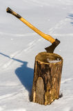 Ax stuck in wood log snow winter Stock Image