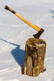 Ax stuck in wood log snow winter Stock Image