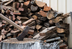 Ax in timber block with firewood Royalty Free Stock Images