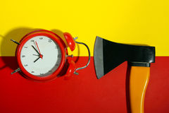 Axe with alarm clock. New axe with a beautiful red wind-up alarm clock on a red and yellow background stock photo