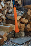 Axe with black and orange handle and firewood Royalty Free Stock Photo