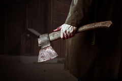 Axe with blood in male hand. Murderer or butcher, halloween theme Stock Photos