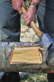 Axe blow. Close up of a forester chopping a beech log, a chip of wood flying and slight motion blur on the hands, axe and chip of wood Royalty Free Stock Photos