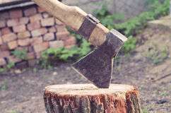 Axe carved in stump in courtyard on a brick background. Ax driven into the wood timber in the yard Stock Photo