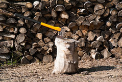 Axe in chopping block. A yellow axe used for chopping firewood with blade in  chopping block2 Stock Photo