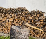 Axe on the chopping block with chopped wood pile leveled on whit Stock Photos