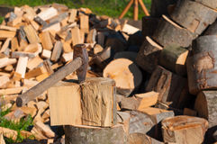 Axe in Chopping Block and Firewood. Ax pile of Stock Image