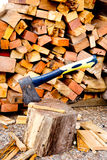 Axe on chopping block in front of wood pile Stock Images