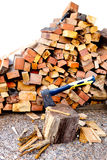Axe on chopping block in front of wood pile Royalty Free Stock Photo