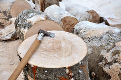 Axe on a chunk of firewood in the snow Stock Photos