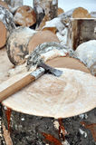 Axe on a chunk of firewood in the snow Royalty Free Stock Images
