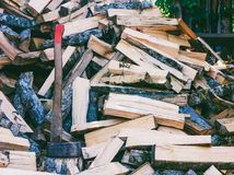 Axe cleaver and a bunch of chopped beech, hornbeam and ash firewood for the stove Royalty Free Stock Photo