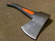Axe Cutting Edge. Black orange coloured with metal single blade head. Concrete pathwalk in the background Royalty Free Stock Photo