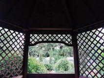 Axe en bois avec le trellis dans le jardin de cottage images stock