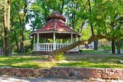 Axe en parc avec un toit en pente se tenant à la nuance des arbres avec l'herbe verte autour Un bon endroit à détendre photo libre de droits