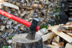 Axe and fire wood. Axe thrust in a birch chock against  woodpile of fire wood Stock Photos