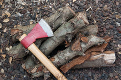 Axe and firewood in the ground Royalty Free Stock Photo