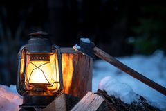Axe, firewood and lantern in the wilderness royalty free stock image