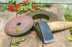 Axe and grindstone. On the wooden table Royalty Free Stock Photos