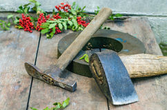 Axe and hummer. Axe, hummer and grindstone on the wooden table Royalty Free Stock Image