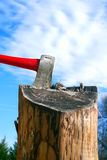 Axe in log. Axe in a splitting log against beautiful blue sky with fluffy clouds stock images