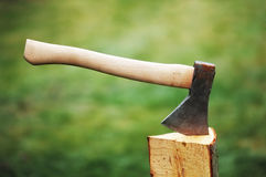Axe in a log on the background of green grass Royalty Free Stock Photos