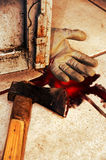 Axe murder. Bloody axe and gardener's gloved hand, lying on the floor close to a rusty door Royalty Free Stock Photos