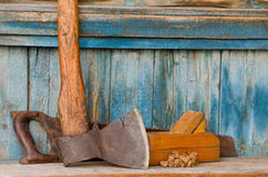 Axe, planer and saw on an old wooden background, chips.  Stock Images