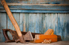 Axe, planer and saw on an old wooden background, chips. Space for text Royalty Free Stock Image