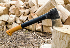 Axe in polene amid piles of logs in the forest Royalty Free Stock Images