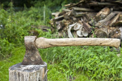 Axe at rest in a block of wood. A woodsman's axe at rest in a block of wood Royalty Free Stock Photos