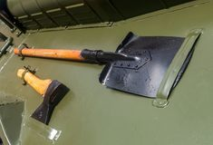 A shovel and an axe on a military car Green royalty free stock photography
