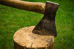 The axe splits a log. The axe hammered into a tree Royalty Free Stock Photos