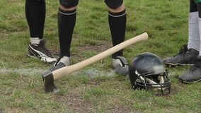 Axe stuck in gridiron field grass, football players ready to compete for trophy. Stock footage stock video