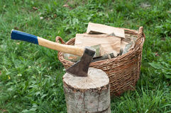 An axe stuck in a log in front of basket with logs fire Royalty Free Stock Photography