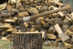An axe stuck in a log in front of a pile of wood Royalty Free Stock Photos