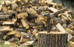 An axe stuck in a log in front of a pile of wood Royalty Free Stock Image