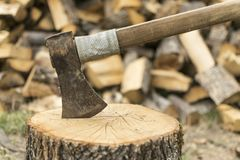 An axe stuck in a log in front of a pile of wood Stock Image