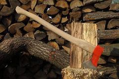 Axe stuck onto a chopping block, wood all around stock photo