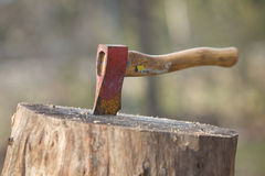 An  axe stuck into wood Royalty Free Stock Photos