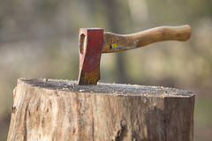 An  axe stuck into wood Royalty Free Stock Images