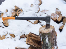 Axe in stump stored firewood in winter. The ax stuck in a tree stump on a background of chopped firewood stored in the winter Royalty Free Stock Photography