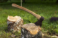 Axe thrust in a log. After puncture grass ax stuck in a log Stock Photography