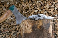 Axe in trunk 1. Axe in a trunk and working gloves in front of a stack of firewood Royalty Free Stock Photo