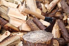 An axe on a wood, tree log. An axe stuck in a log in front of a pile of wood, ready for chopping and winter. Stock Photos