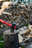 Axe and woodpile. Axe thrust in a birch chock against  woodpile of fire wood Royalty Free Stock Photo