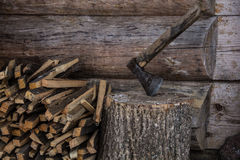 Axe and woodpile. Wood handled axe beside split logs outside a log cabin Stock Images